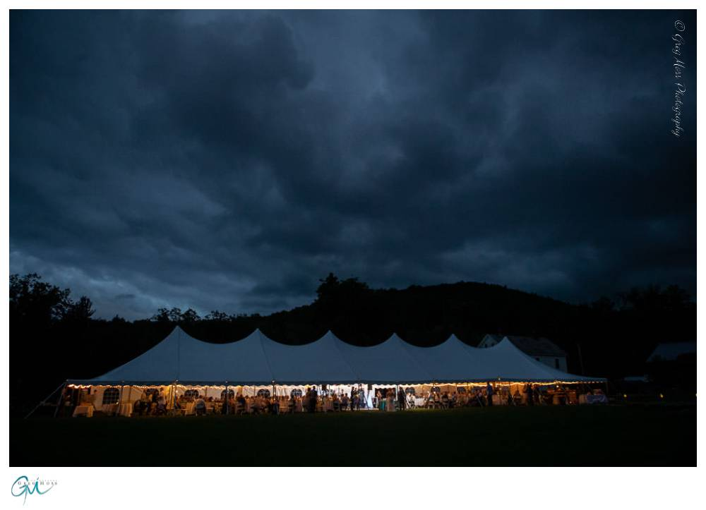 Lit up tent at night with dramatic clouds