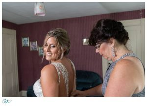 Mother of the bride helping zip up the wedding dress.