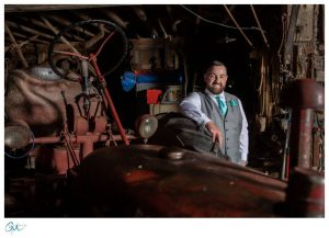 Groom in barn leaning on rusted tractor