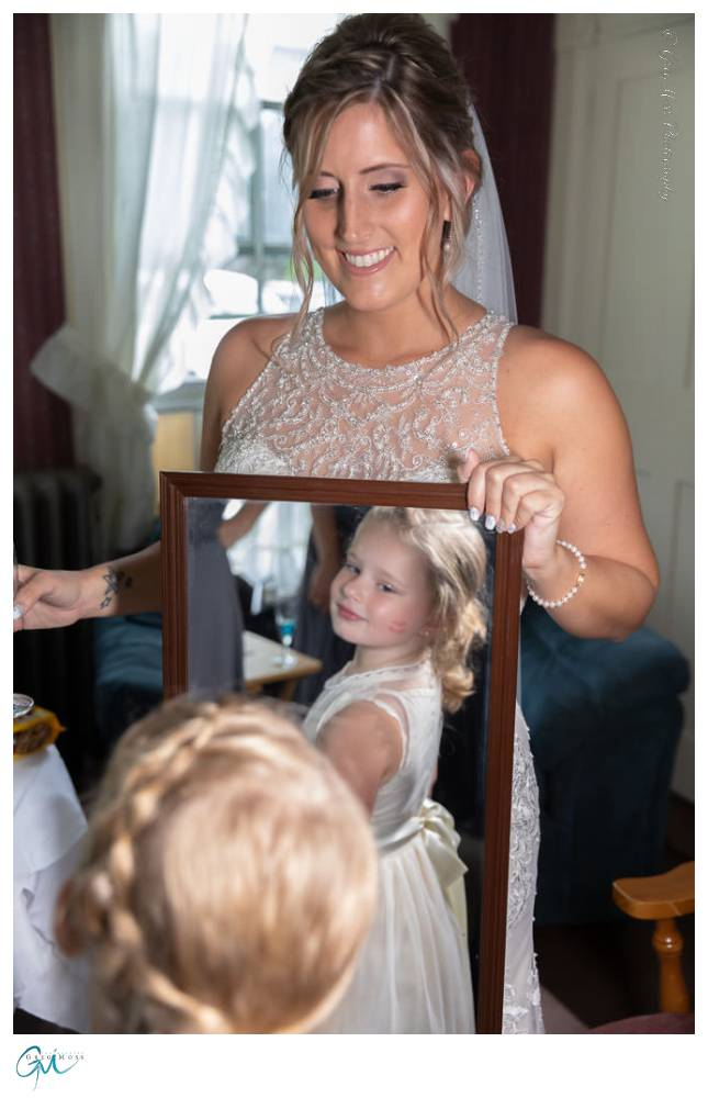 Bride with flower girl looking into mirror.