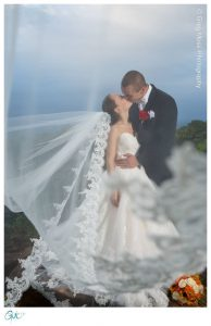 Bride and groom kissing on mountain view with veil in foreground