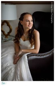 Bride leaning on chair looking out window