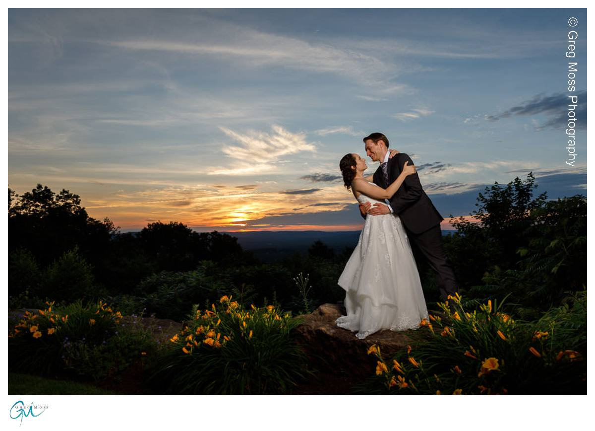 Groom dipping bride at sunset