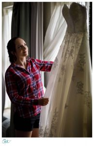 bride looking at wedding dress in window