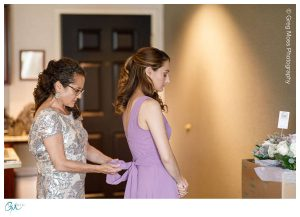 Mother of the bride tying bow on the back of bridesmaid dress