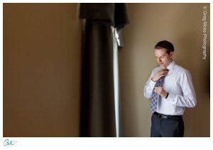 Groom getting ready tying his tie