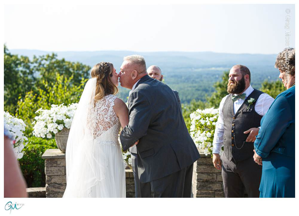 Father kissing bride as he gives her away at alter