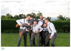 Groomsmen in suspenders and bowties lifting groom up