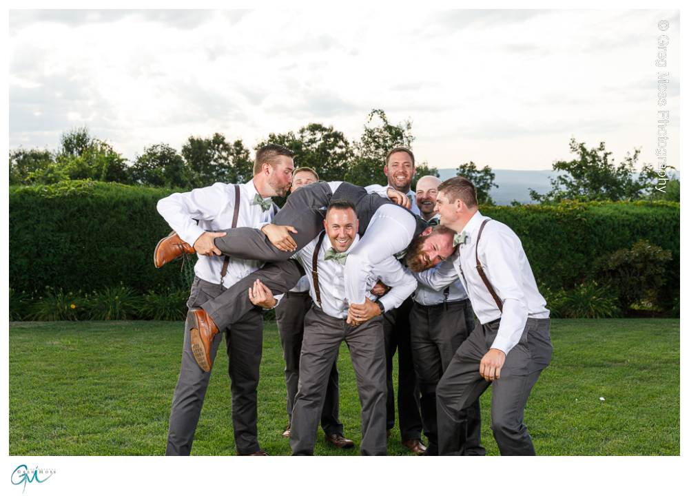 Groomsmen in suspenders and bowties lifting groom up