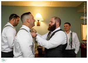 Groom helping groomsmen with his tie
