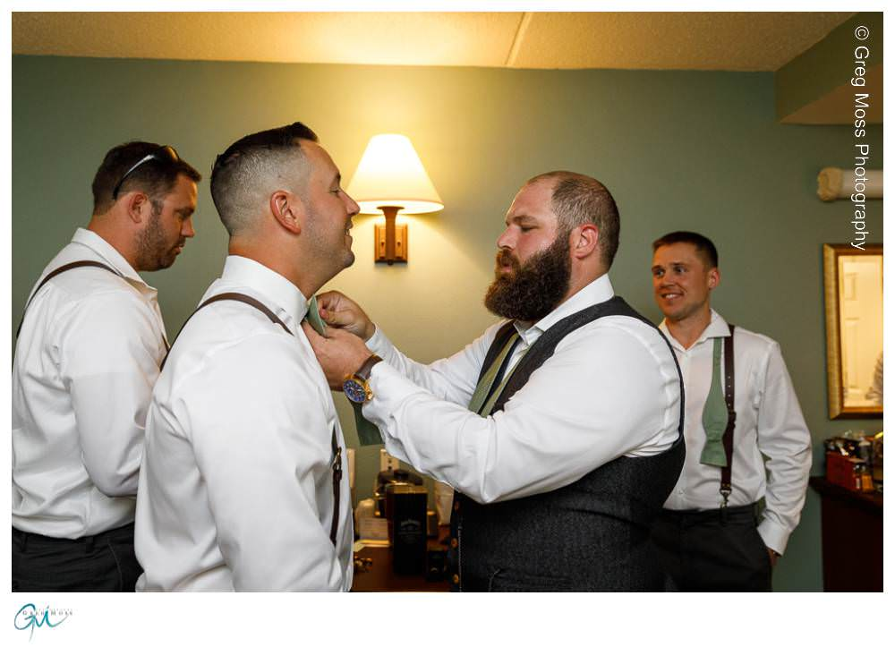 Groom helping groomsmen with his tie