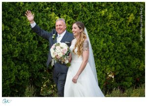 Father walking bride down the aisle during outdoor ceremony