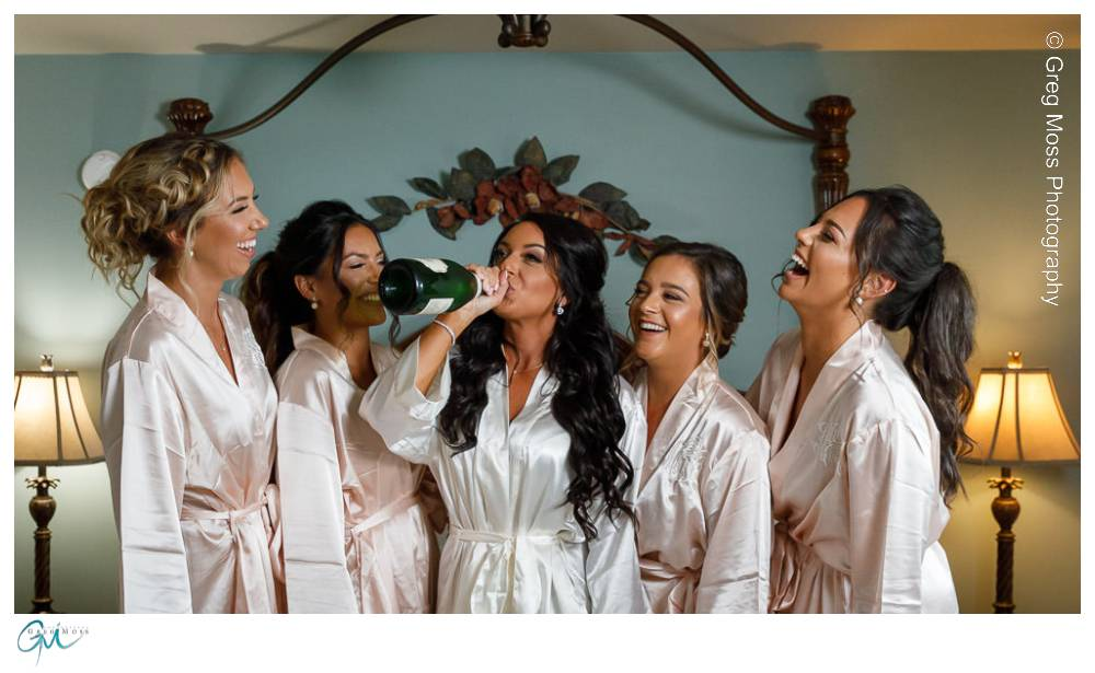 Bride drinking champagne out of the bottle with bridesmaids in matching robes