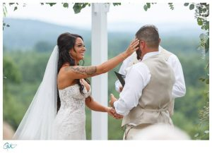 Bride wiping tear from grooms face during ceremony