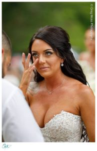Bride wiping tear during ceremony