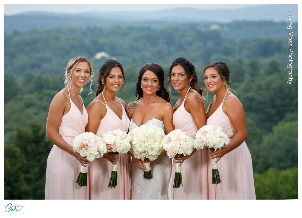Pretty bridesmaids in pink dresses with flowers.