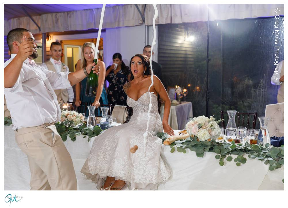 Groom popping champagne in front of bride with surprised expression