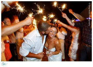 Groom kissing bride surrounding by sparklers during exit from the reception