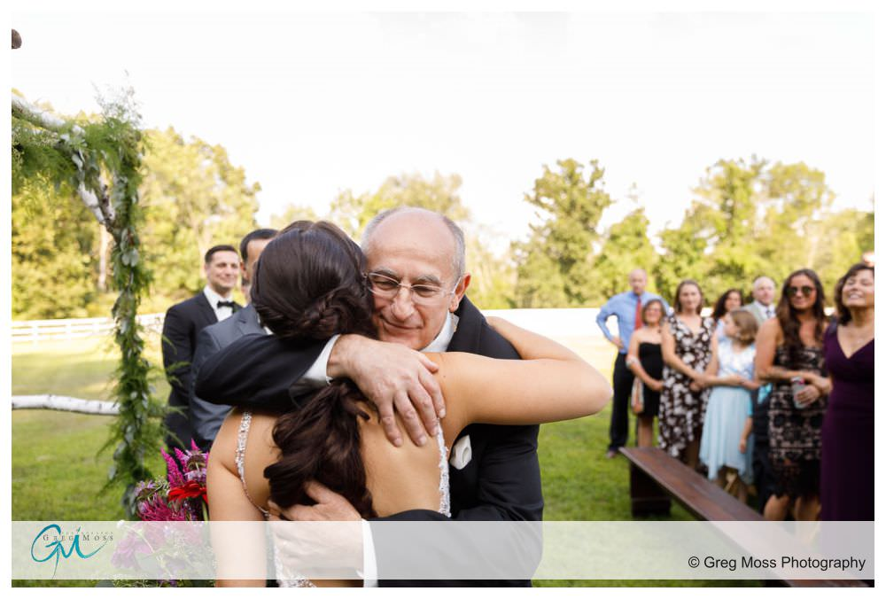 Father hugging bride as he gives her away during outside ceremony