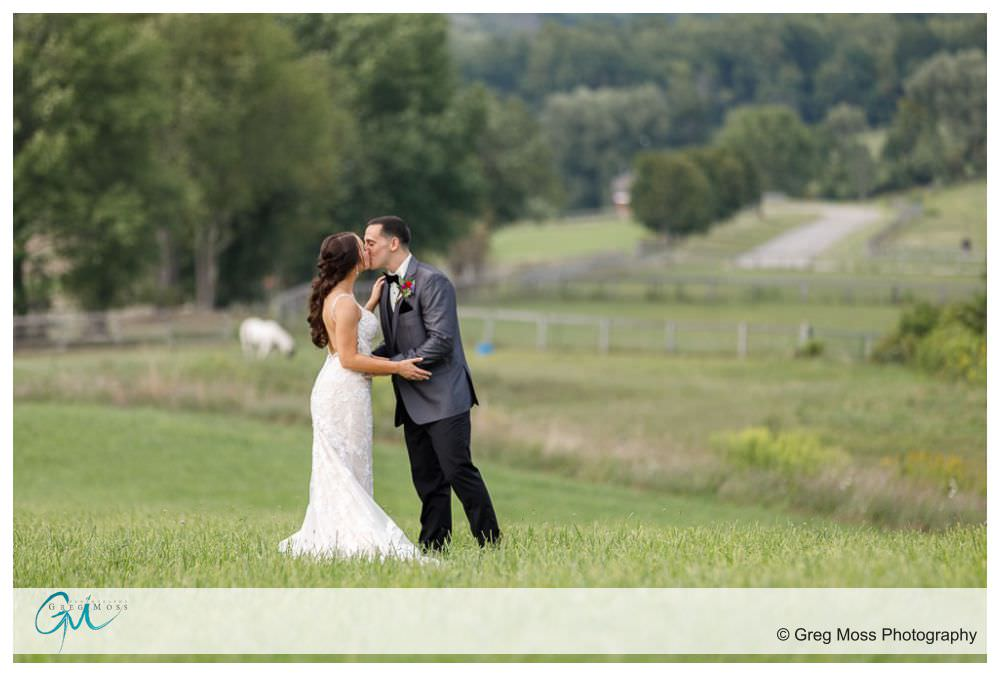 wedding day portrait of bride in groom in field with pastures in background