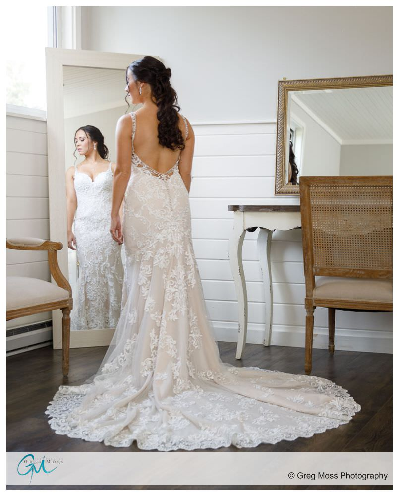 Full length photo of bride in wedding dress looking into mirror