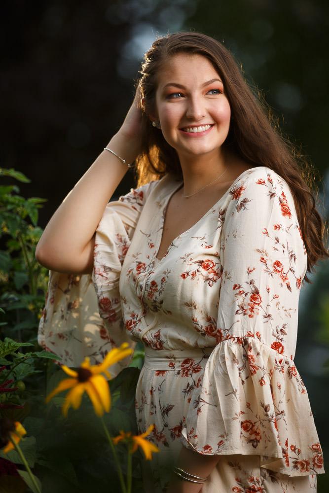 High School Senior in flower garden with sunlight behind her