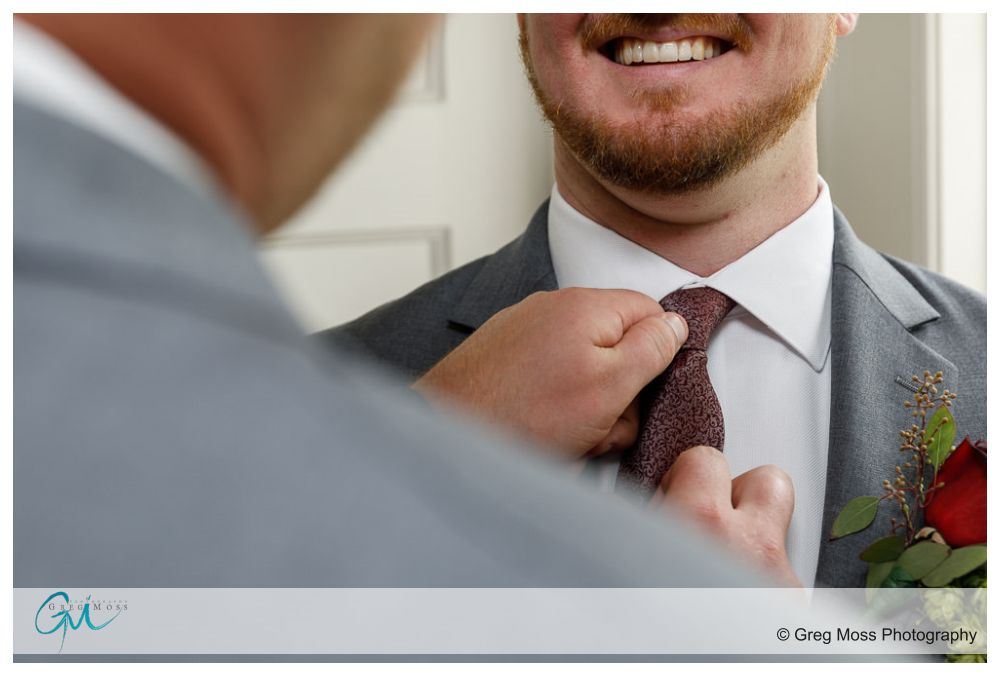 Father of groom helping groom with tie