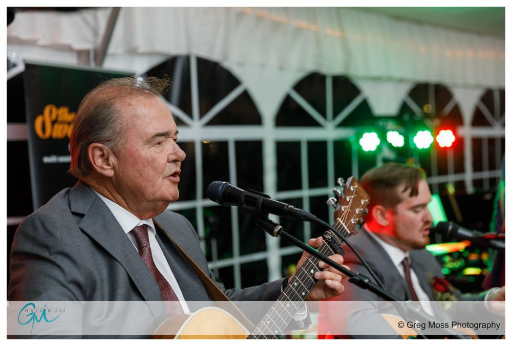 Groom and father playing guitars and singing at his wedding reception