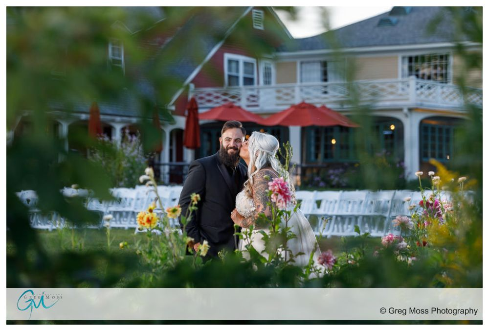 Bride and Groom Framed by flowers with Salem Cross Inn in the background