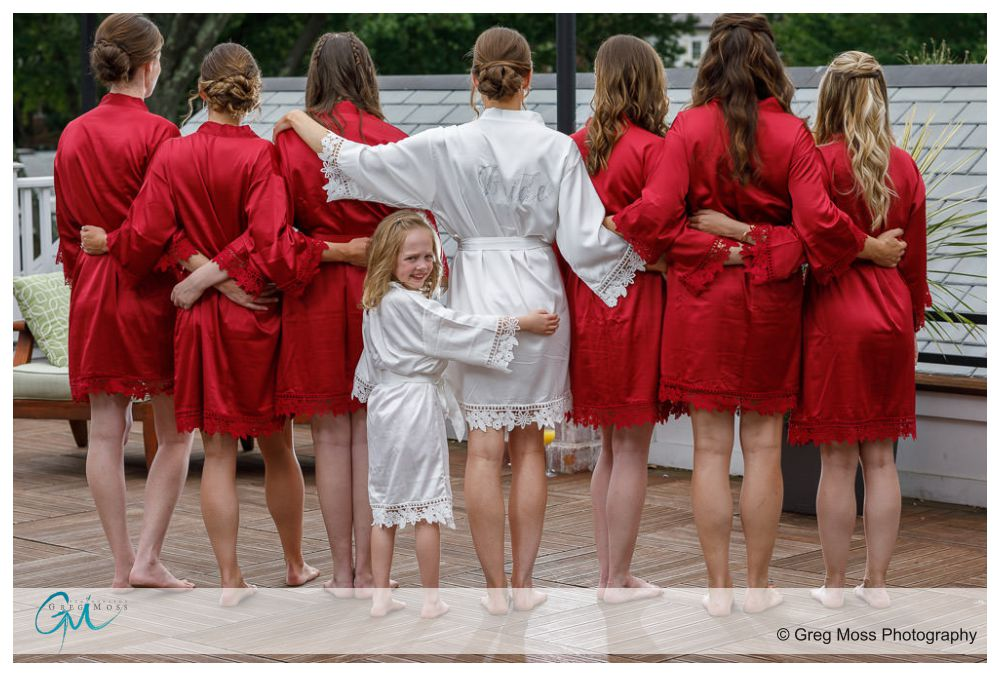 Bridesmaids in robes with back to camera with flower girl looking over here shoulder
