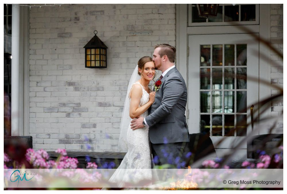 Bride and Groom in front of building with fireplace in front of them