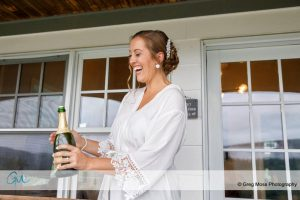 Bride in white robe opening champagne bottle