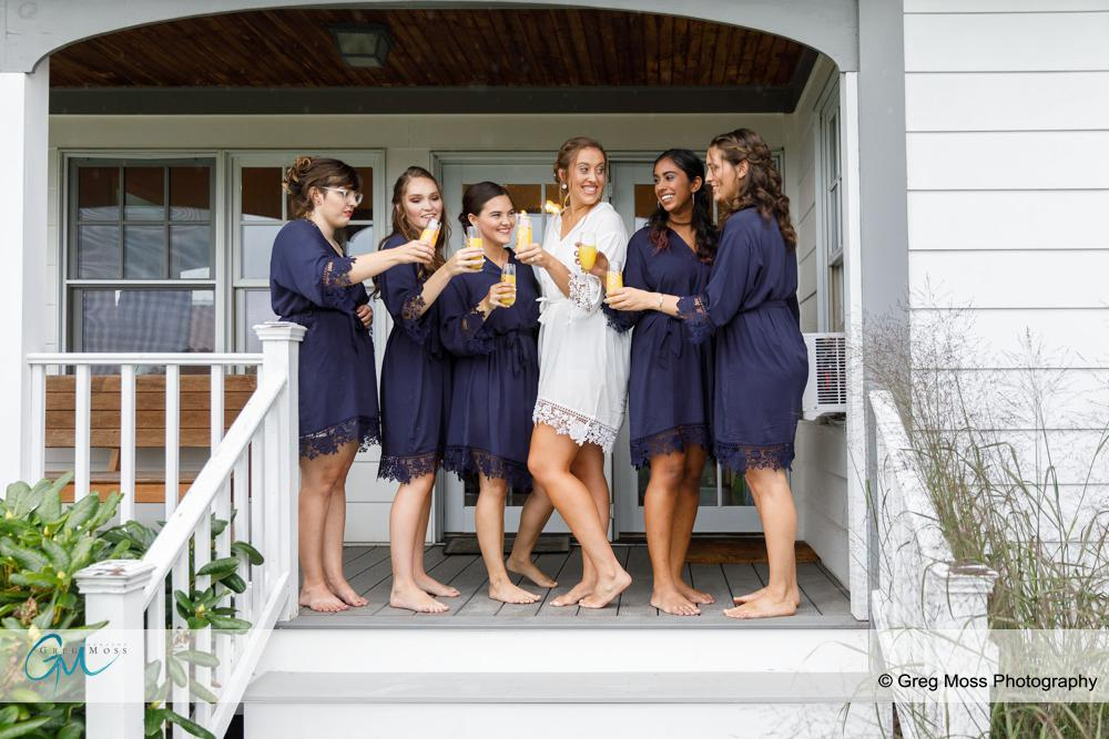 Bride and Bridesmaids in matching robes toasting with Mimosas