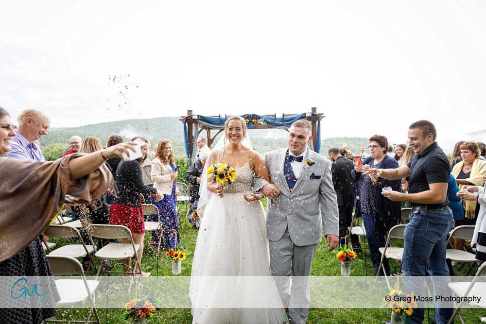 Guests throwing confetti while bride and groom walk down the aisle during outdoor ceremony
