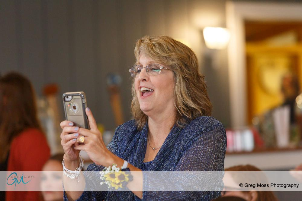 Mother of the bride taking photo of first dance with cell phone