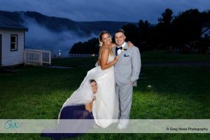 Bride and groom with maid of honor hiding in brides dress.