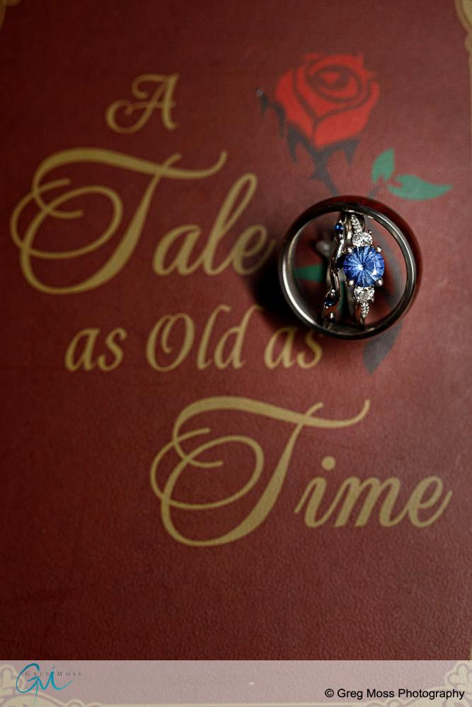Photo of blue wedding ring on a book called Tale as old as time