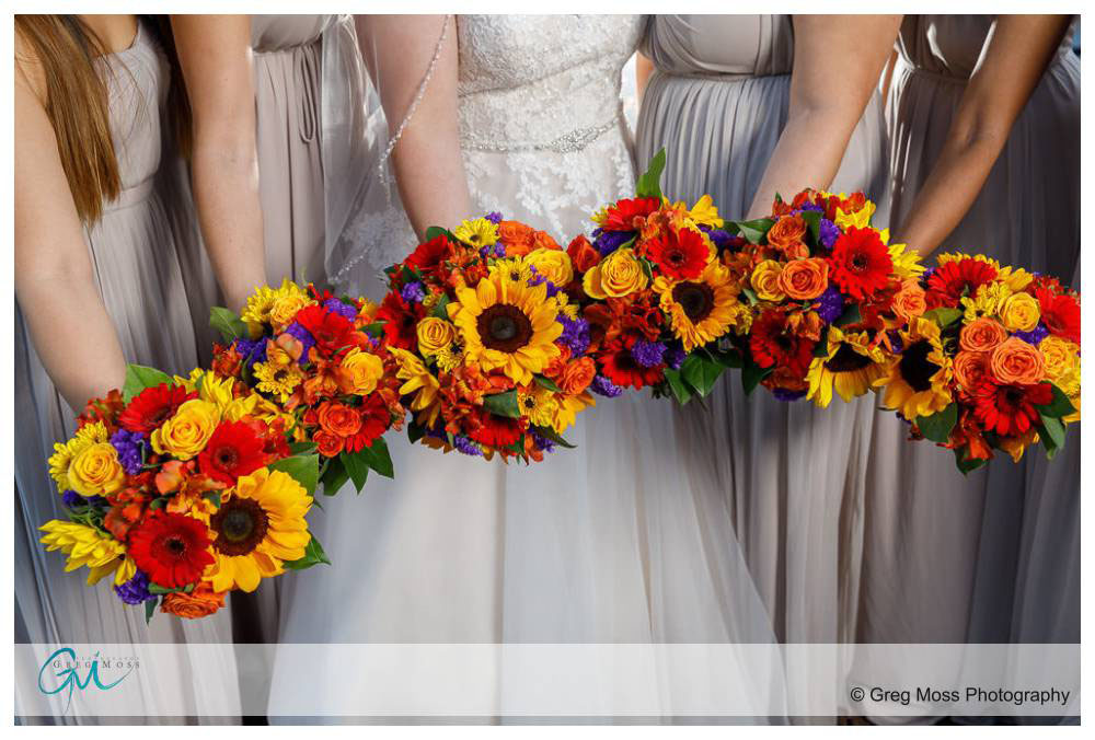 Bride and bridesmaids holding flowers together