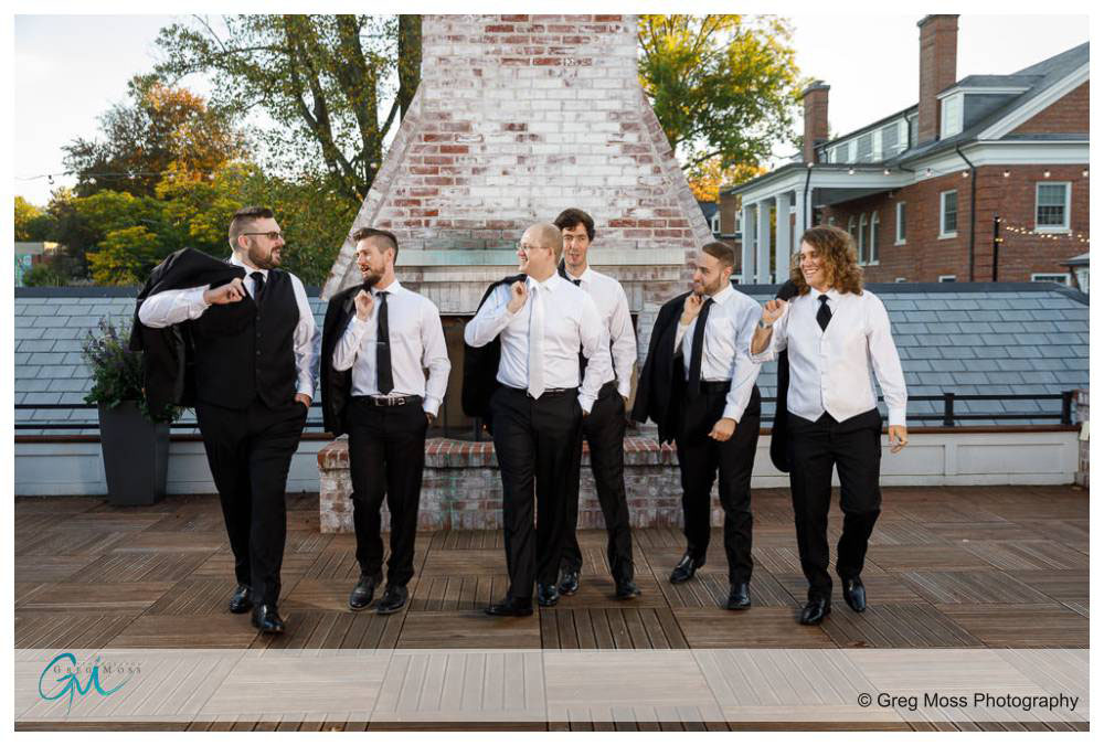 Groom and Groomsmen walking with suit jackets over their shoulders.