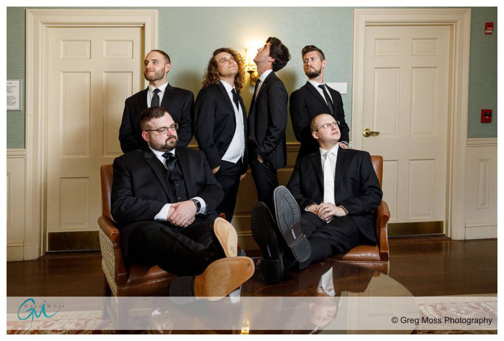 Groom and groomsmen posed on chairs outside of graves room at Inn on Boltwood