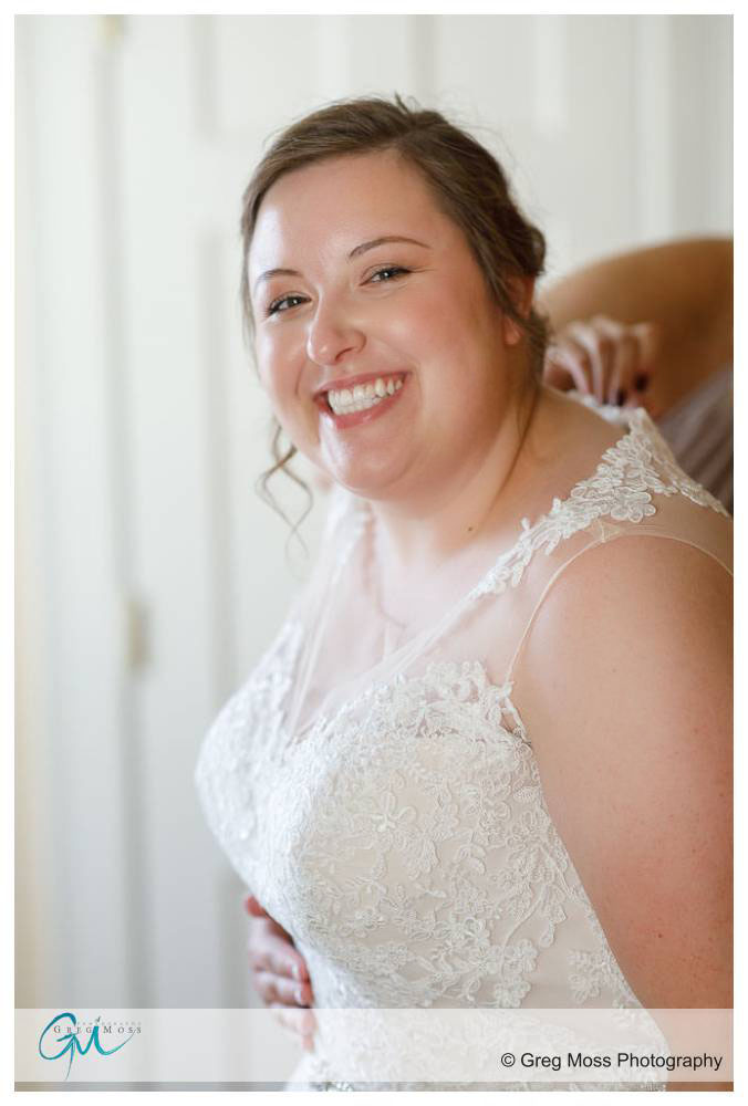 Bride smiling while maid of honor buttons up the dress.