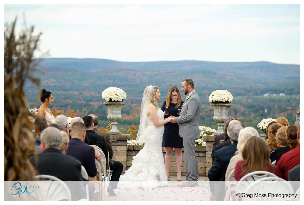 Bride and Groom holding hands at outside at the alter overlooking valley with fall foilage