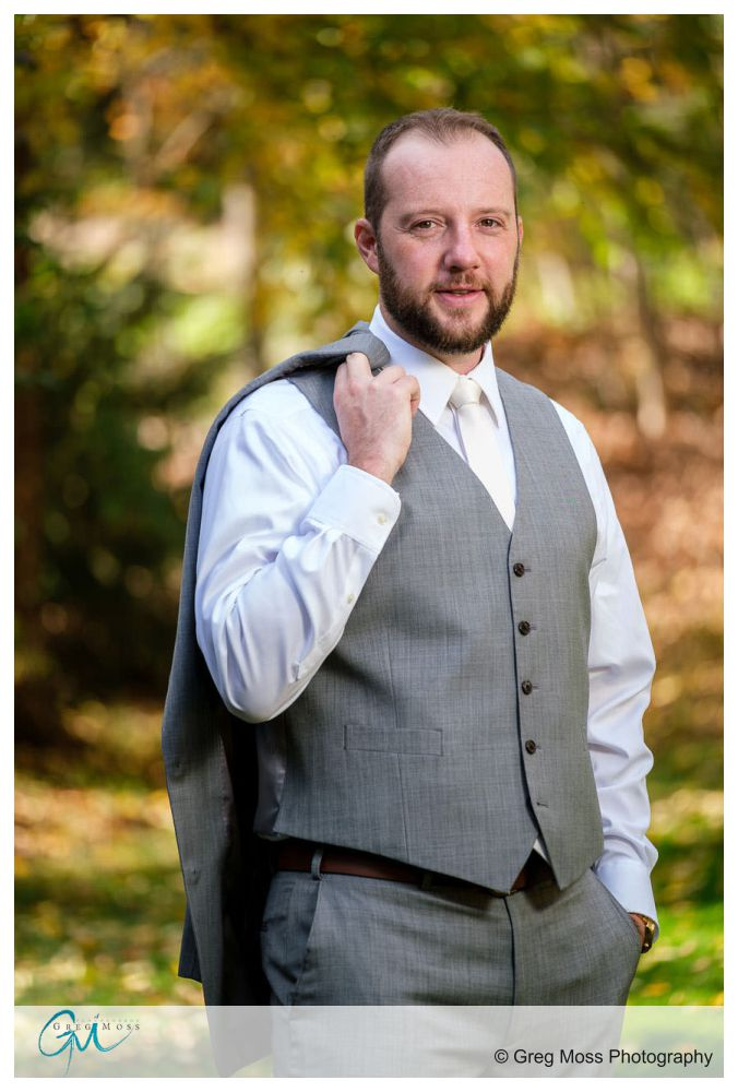 Groom posing with jacket draped over shoulder