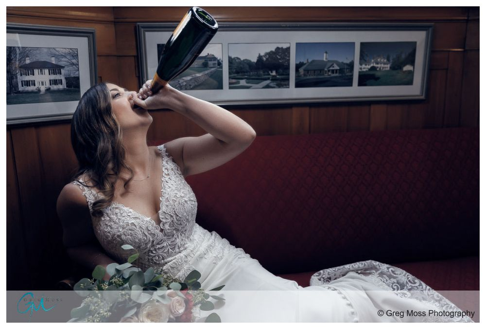 Bride laying on red couch with bridal bouquet while jugging bottle of champagne
