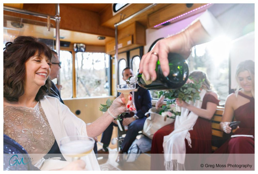 Groom filling mom's champagne glass on their ride on the trolley to the mansion on bald hill