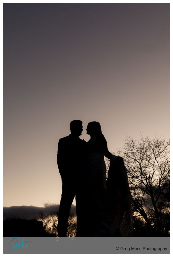a silhouette of the bride and groom standing on ledge with the bride holding her train