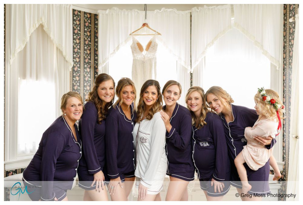Bride in white robe and bridesmaids in blue pajamas with the brides dressing hanging in the background