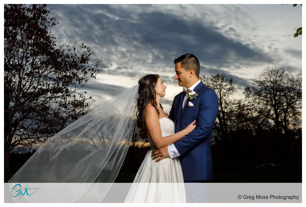 Bride and Groom portrait with veil flowing in the wind and dramatic sky in the background