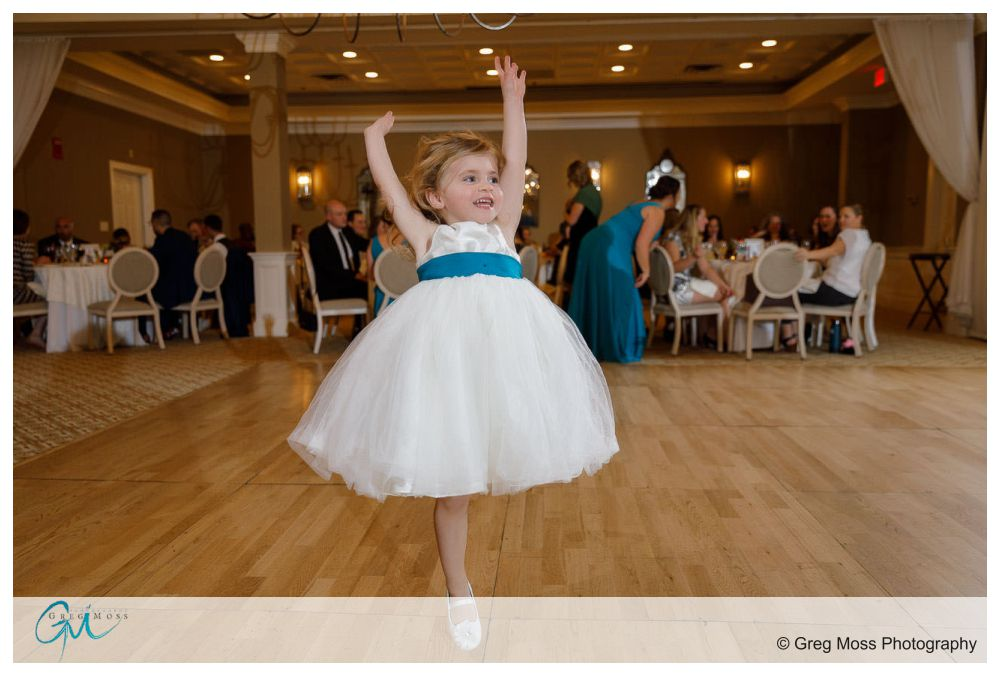 Flower girl jumping in the air dancing during wedding reception