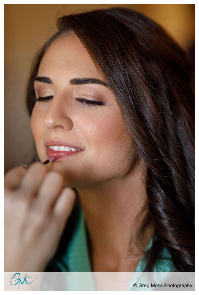 Bride having lipstick applied on wedding day